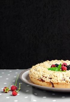 Torta di pasta frolla fatta in casa ai frutti di bosco con crumble su piastra e panno grigio punteggiato su fondo nero