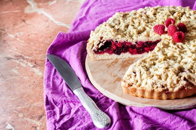 Torta di pasta frolla fatta in casa ai frutti di bosco con crumble su tavola di legno e panno viola
