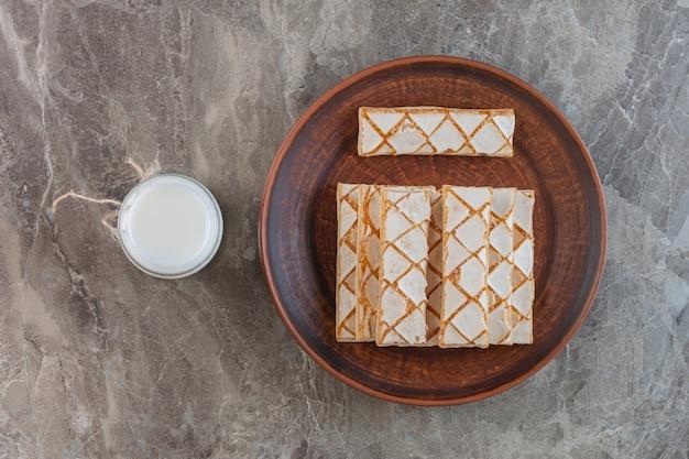 Biscotti fatti in casa con una tazza di latte su grigio.