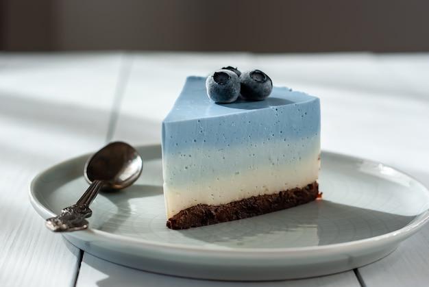 Cheesecake fatta in casa di piselli farfalla blu con frutti di bosco freschi su un tavolo luminoso
