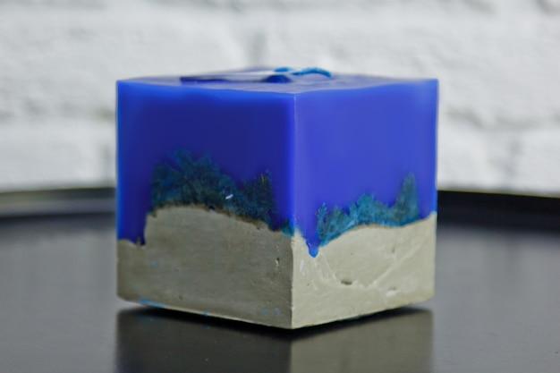 Candela blu fatta in casa con cemento sulla superficie di un muro bianco
