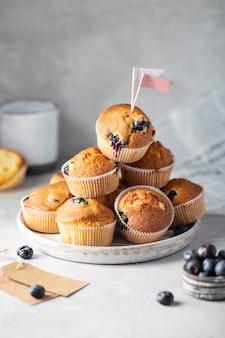 Muffin ai mirtilli fatti in casa su un piatto sfondo grigio verticale