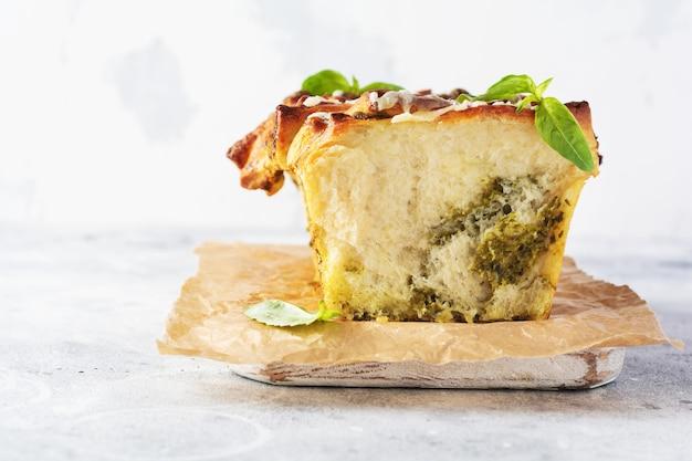 Pane al pesto intrecciato fatto in casa guarnito con foglie di basilico su tavolo luminoso e carta pergamena. pane tradizionale italiano. copia spazio. vista dall'alto.