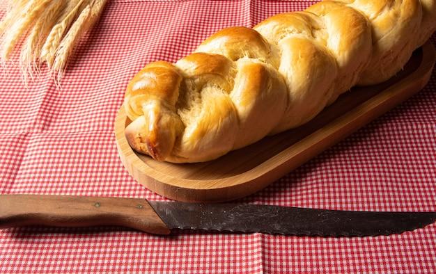Pane fatto in casa, pane intrecciato su legno e una tovaglia a quadretti bianchi e rossi, un coltello e un ramo di grano.