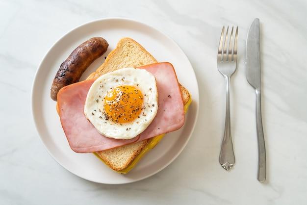 Pane fatto in casa formaggio tostato condito con prosciutto e uovo fritto con salsiccia di maiale per colazione