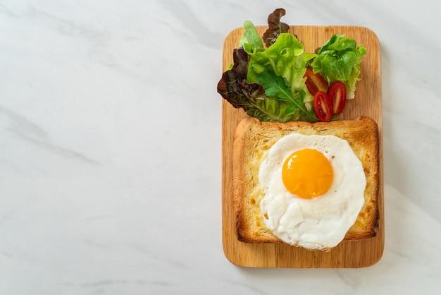 Pane casereccio tostato con formaggio e uovo fritto sopra con insalata di verdure per colazione
