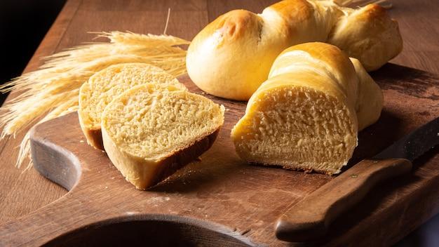 Pane fatto in casa, due bei pani fatti in casa uno di loro a fette su legno e un ramo di grano.