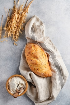 Pane fatto in casa con semi sul tavolo in pietra di cemento grigio chiaro, farina di frumento e spighe.