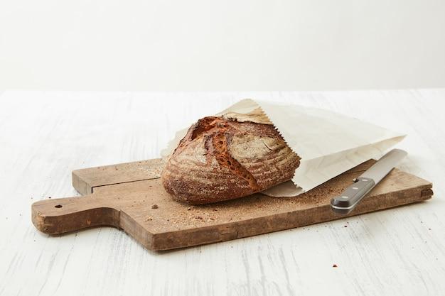 Pane fatto in casa avvolto in carta su una tavola di legno con un coltello su uno sfondo chiaro