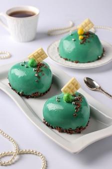 Mousse luminose fatte in casa torte cuori con glassa specchio verde su sfondo bianco, primo piano, orientamento verticale