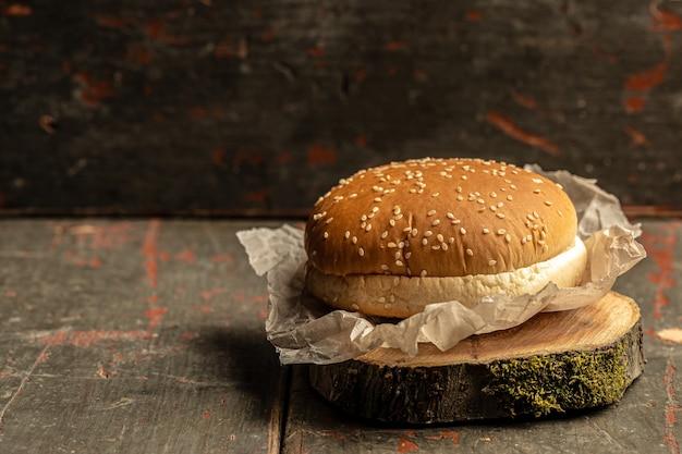 Panino di hamburger fatto in casa con sesamo su fondo di legno rustico. fast food e concetto di cibo spazzatura, banner, menu, luogo di ricette per il testo