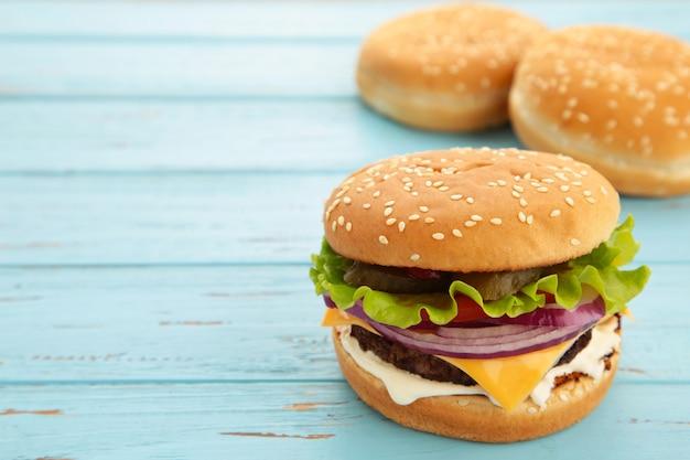 Ingredienti per hamburger fatti in casa disposti sulla parete di legno blu. vista dall'alto