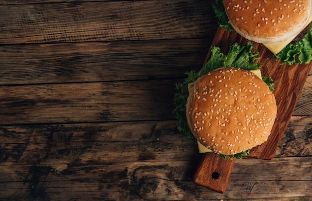 Hamburger fatto in casa con manzo, pomodoro, formaggio e lattuga su tavola di legno. vista dall'alto con copia spazio