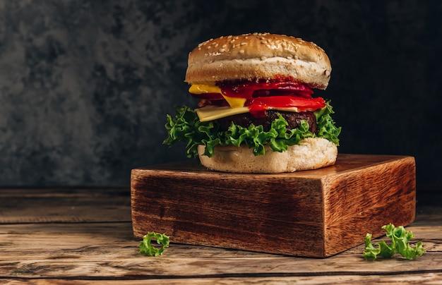 Hamburger fatto in casa con manzo, pomodoro, formaggio e lattuga su scatola di legno. messa a fuoco selettiva