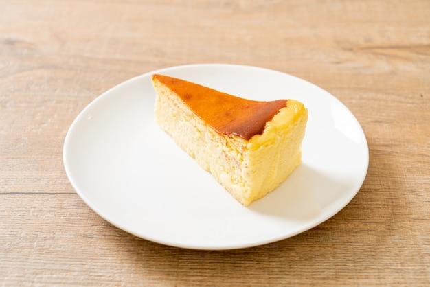 Torta di formaggio casalinga dell'ustione sulla zolla bianca