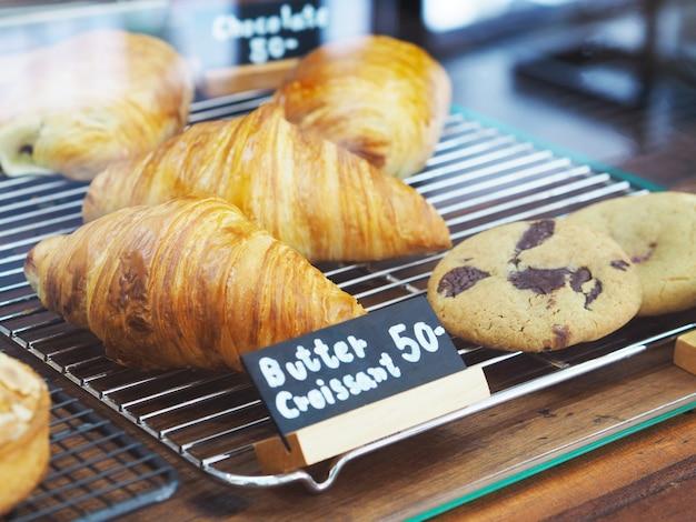 Croissant al burro fatto in casa e biscotti con etichetta nera in vetrina al negozio di panetteria.