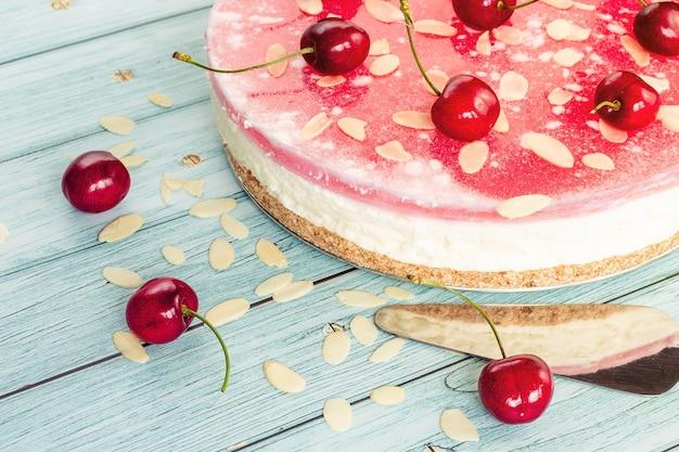 Torta fatta in casa, cheesecake con ciliegie fatte a mano in primo piano, ciliegie sparse con scaglie di cioccolato su una superficie chiara