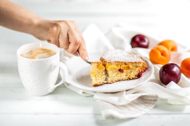 Torta fatta in casa preparazione del cibo torta dolce di frutta con albicocche e prugne. mano femminile che interrompe un pezzo di torta con una forchetta