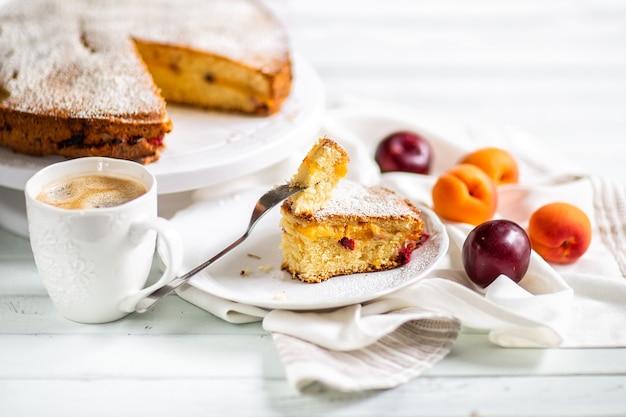 Torta fatta in casa preparazione del cibo torta dolce di frutta con albicocche e prugne. tavolo servito con caffè e torta. articoli da cucina
