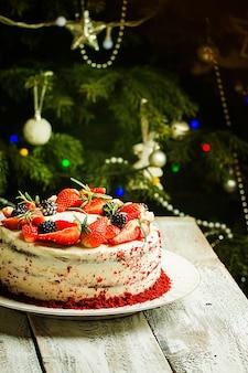 Torta fatta in casa red velvet decorata con crema e frutti di bosco sopra l'albero di natale