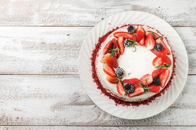 Torta fatta in casa red velvet decorata con crema e frutti di bosco su superficie di legno bianca, vista dall'alto