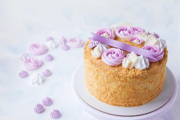 Torta fatta in casa in una spolverata, decorata con meringhe di colore lilla e rosa. bella torta su sfondo bianco per compleanno, anniversario