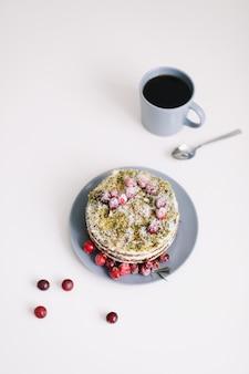 Torta fatta in casa con frutti di bosco e tazza di tè sul tavolo bianco