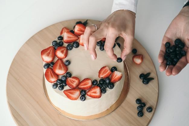 Torta fatta in casa con crema di formaggio e frutti di bosco freschi il pasticcere decora la torta con fragole e mirtilli torta di crema bianca minimalista