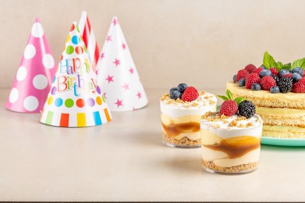 Torta fatta in casa con frutti di bosco freschi e cappello di compleanno su sfondo luminoso.