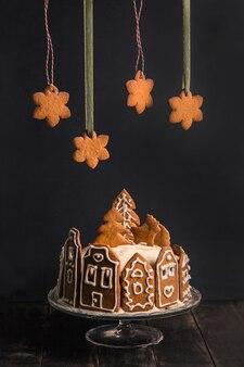 Torta fatta in casa con facciate di panpepato di case di città, un albero di natale e cervi su supporto di vetro, sopra di esso sono sospesi fiocchi di neve di panpepato.