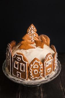 Torta fatta in casa con facciate di panpepato di case di città, un albero di natale e cervi su supporto in vetro e tavolo in legno.