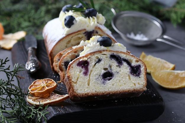 Torta fatta in casa con limone e mirtillo cosparsa di zucchero a velo e guarnita con crema biscotto su tavola di legno su fondo grigio. avvicinamento