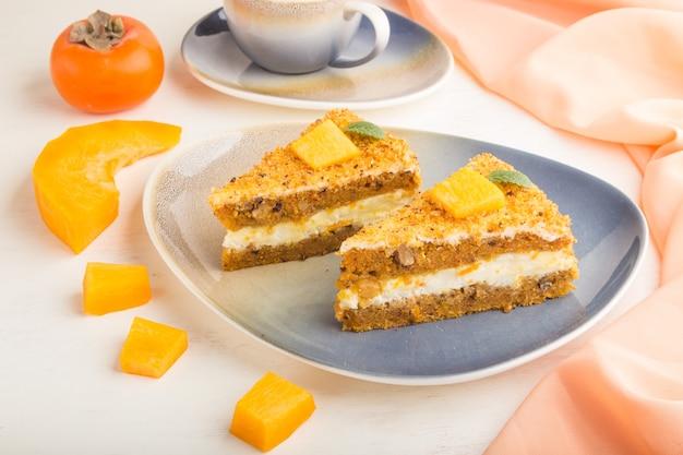 Torta fatta in casa con cachi e zucca e una tazza di caffè su una superficie di legno bianca con tessuto arancione