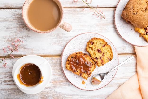 Torta fatta in casa con uvetta, mandorle, caramello morbido e una tazza di caffè su un fondo di legno bianco e tessuto di lino arancione. vista dall'alto, laici piatta, da vicino.