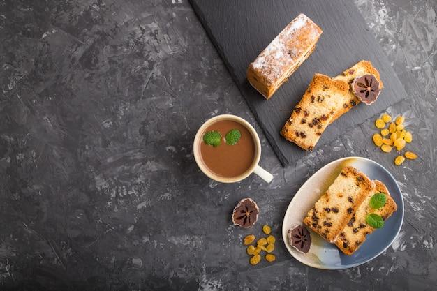 Torta fatta in casa con uvetta, cachi secchi e una tazza di cioccolata calda su uno sfondo di cemento nero. vista dall'alto, copia spazio.