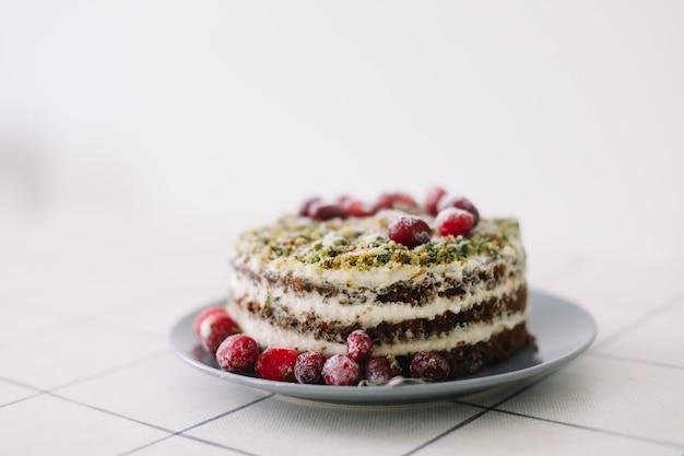 Torta fatta in casa con spinaci e crema decorata con mirtilli rossi freschi sul tavolo bianco