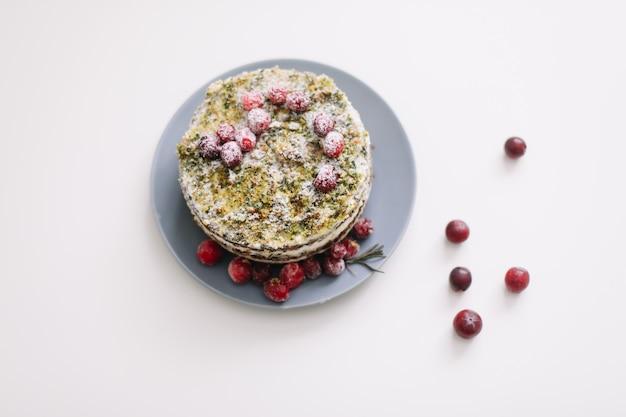 Torta fatta in casa con spinaci e panna decorata con mirtilli rossi freschi