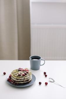 Torta fatta in casa con frutti di bosco e una tazza di tè