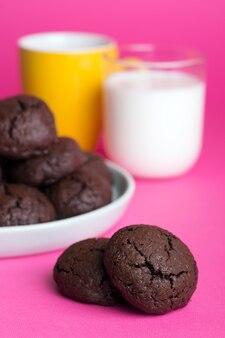 Torte fatte in casa - biscotti con gocce di cioccolato deliziosi e gustosi con una tazza di latte su uno sfondo luminoso