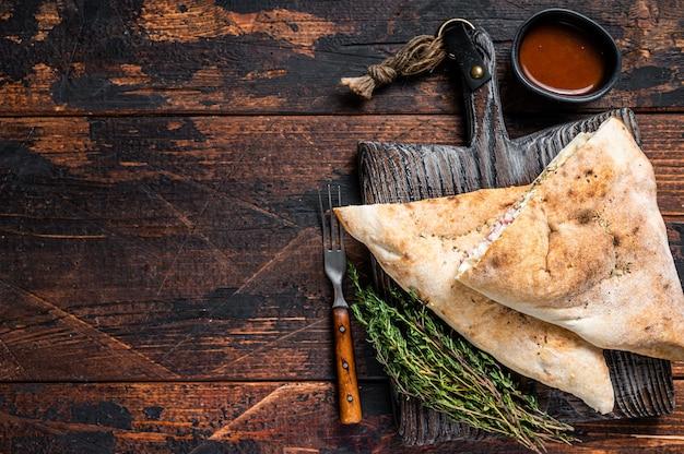 Pizza chiusa calzone fatta in casa con prosciutto e formaggio su tavola di legno. fondo in legno scuro. vista dall'alto. copia spazio.