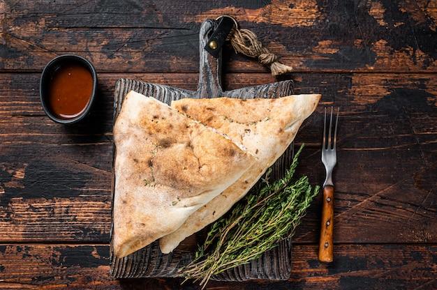 Pizza chiusa calzone fatta in casa con prosciutto e formaggio su tavola di legno. fondo in legno scuro. vista dall'alto.