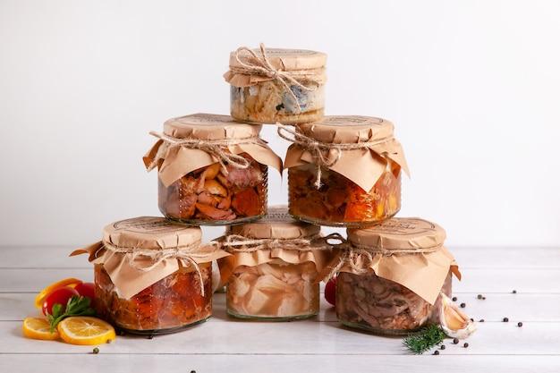 Carne in scatola fatta in casa da pollame di fattoria: oca, anatra, pollo, maiale e manzo, pesce in scatola di sgombro. una piramide di lattine di vetro con cibo in scatola.