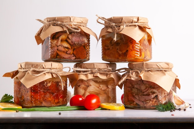 Carne in scatola fatta in casa da pollame di fattoria: oca, anatra, pollo, maiale e manzo. una piramide di lattine di vetro con cibo in scatola.