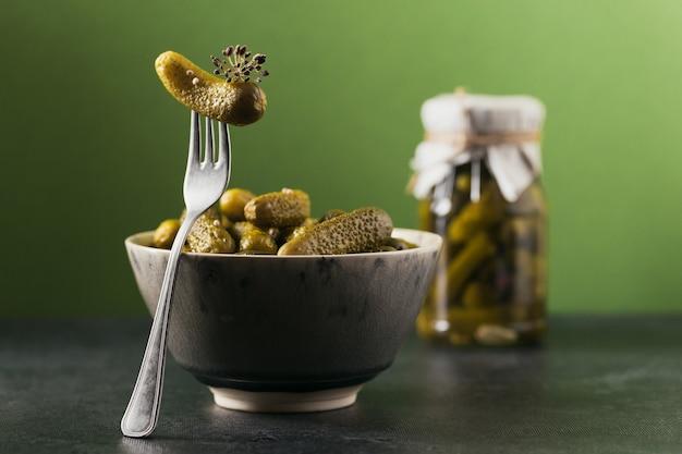 Conserve fatte in casa. cetrioli marinati cetriolini con aneto e aglio in un barattolo di vetro sullo sfondo verde. insalate di verdure per l'inverno.
