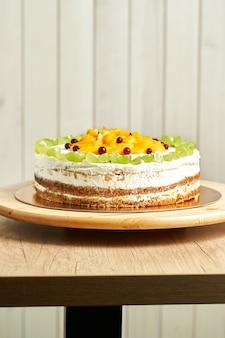 Torta al caramello fatta in casa con frutta. fondo in legno.