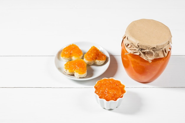 Marmellata di carote fatta in casa in un barattolo di vetro e ciotola su un fondo di legno bianco