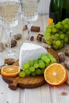 Formaggio fatto in casa con uva e un bicchiere di champagne