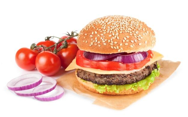 Cheeseburger fatto in casa con polpette di manzo, insalata fresca, pomodori e cipolla su panini al mare isolati