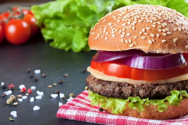 Cheeseburger fatto in casa con polpette di manzo, insalata fresca, pomodori e cipolla su panini di seasame, serviti su un tavolo di ardesia nera.