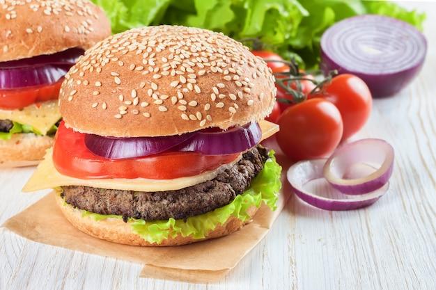 Cheeseburger fatto in casa con polpette di manzo, insalata fresca, pomodori e cipolla su panini al mare, serviti sul tavolo di legno bianco.